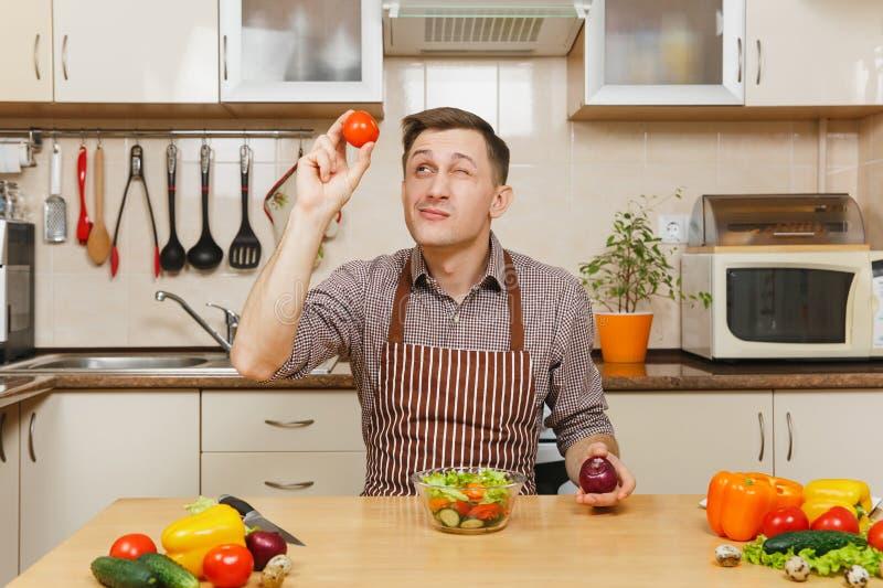 Stilig caucasian ung man som sitter på tabellen Sund livsstil casserole som lagar mat läckert home hemlagat recept mat förbereder arkivfoto