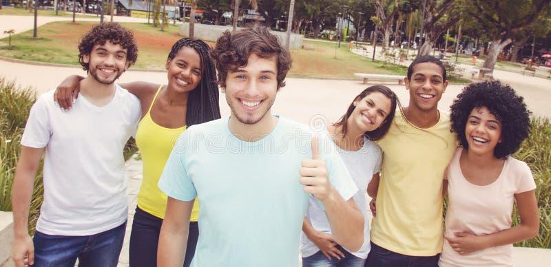 Stilig caucasian ung vuxen människa med gruppen av vänner i retro lo royaltyfria bilder