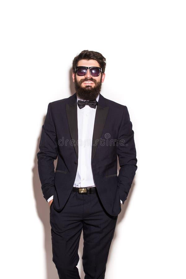 Stilig dräkt och exponeringsglas för ung man som bärande håller händer i fack och ser kameran fotografering för bildbyråer