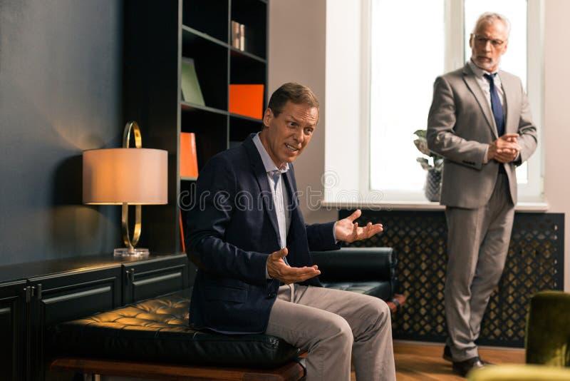 Stilig elegant allvarlig psykoterapeut som bedömer hans patients hälsa royaltyfri fotografi