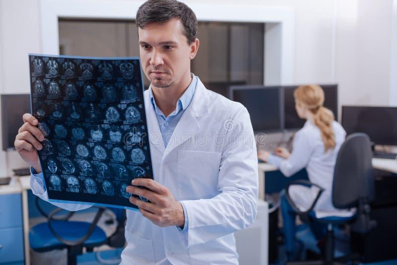 Stilig erfaren doktor som sätter en diagnos royaltyfri bild