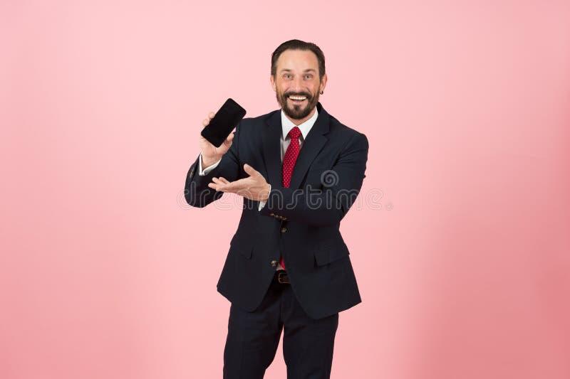 Stilig försäljningsman i dräkten och det röda bandet som visar hans telefon till kameran och pekar till den Gör affären online-ly arkivfoton