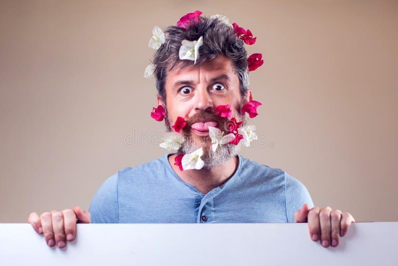 Stilig förvånad man med blommor på skägg och hår Folk, sinnesrörelser, sommar eller vårbegrepp royaltyfri fotografi