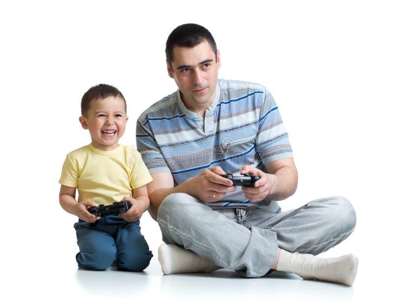 Stilig fader och hans gullig liten son som spelar den modiga konsolen och isolerat le royaltyfri bild