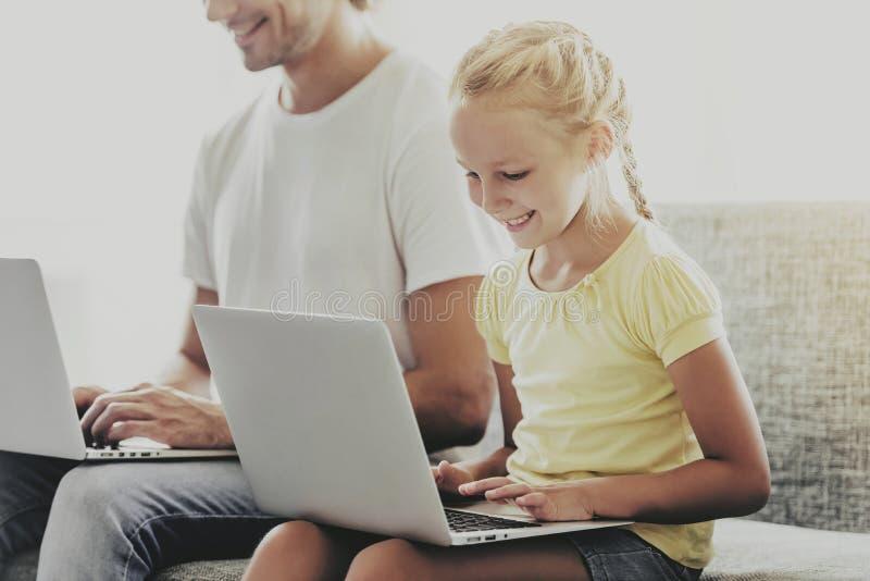 Stilig fader och liten dotter som använder bärbara datorer royaltyfri foto