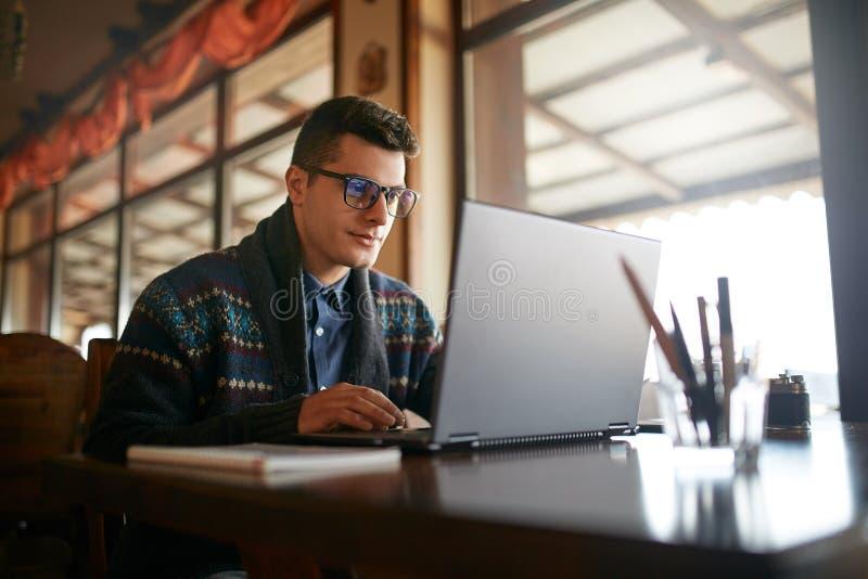 Stilig freelanceraffärsman som arbetar på bärbara datorn i kafé Bloggermannen som uppdaterar hans profil i samkväm, knyter kontak arkivfoto