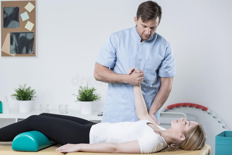 Stilig fysioterapeut som arbetar med patienten royaltyfri fotografi