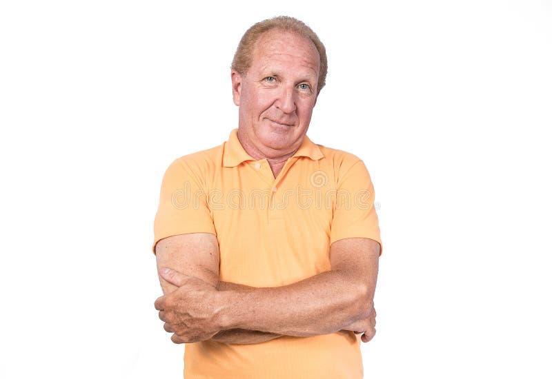 Stilig gamal man med orange korsade polo-skjorta händer royaltyfri fotografi