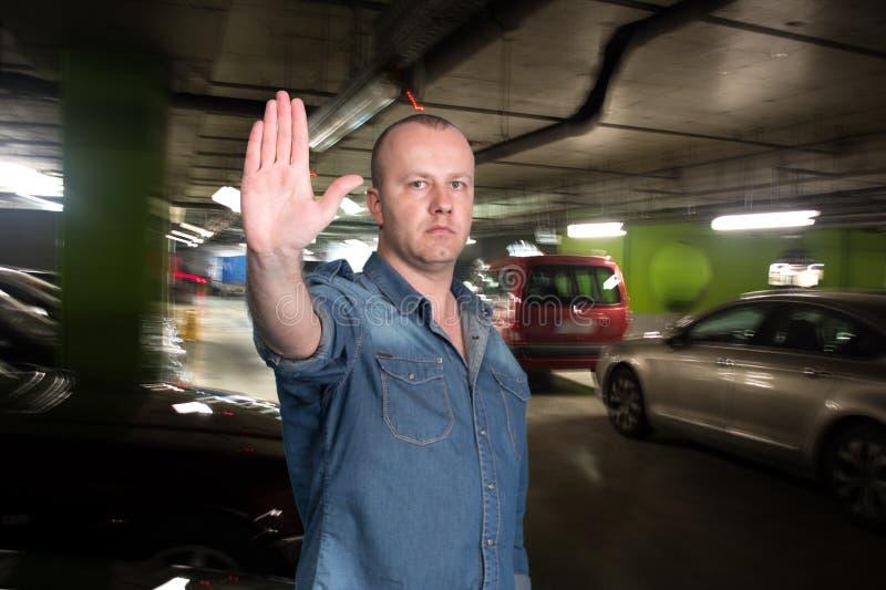 Stilig gest för mandanandestopp i parkeringsgaraget royaltyfria bilder