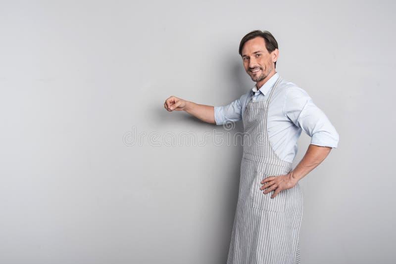 Stilig glad ung man som gör en gest i ett förkläde fotografering för bildbyråer
