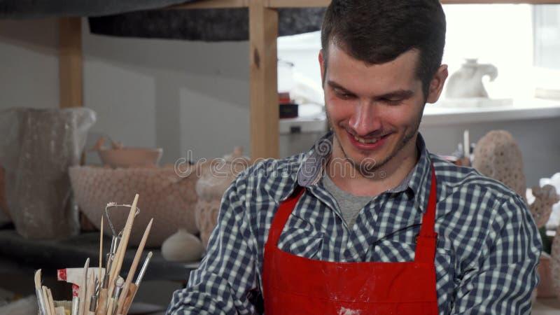 Stilig gladlynt manlig keramiker som tycker om att arbeta på hans studio fotografering för bildbyråer