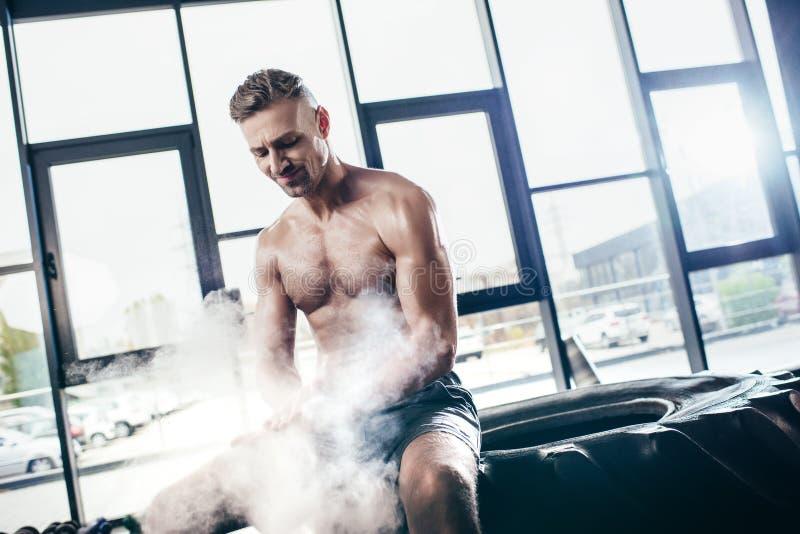 stilig gladlynt shirtless idrottsman som sitter på gummihjulet och applicerar talkpulver på händer royaltyfri fotografi