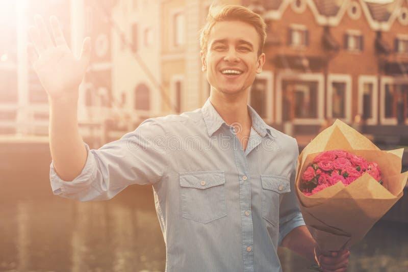 Stilig grabb i tillfällig kläder som håller blommor royaltyfri bild
