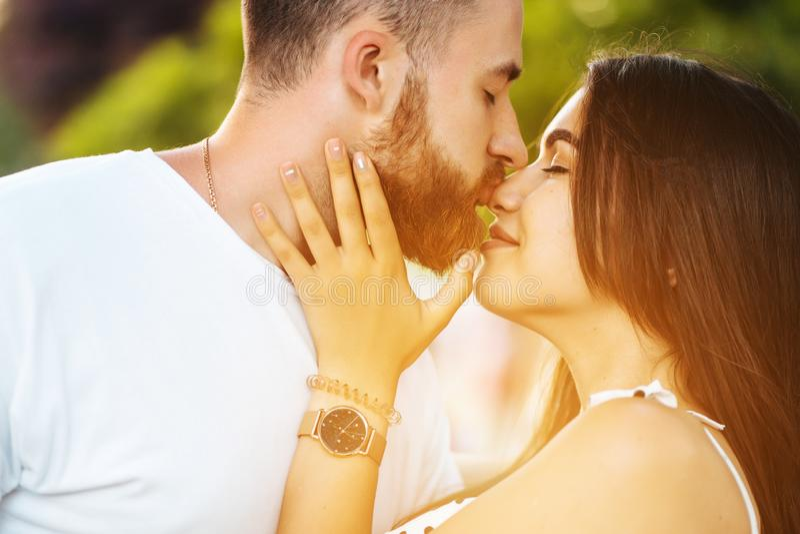 Stilig grabb och härliga flickor som kysser i parkera arkivfoto