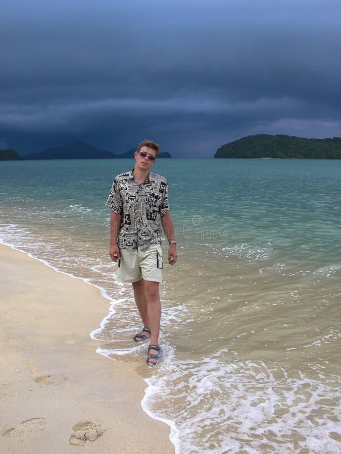 Stilig grabb p? en exotisk strand g? p? stranden f?r tropiskt regn arkivbild
