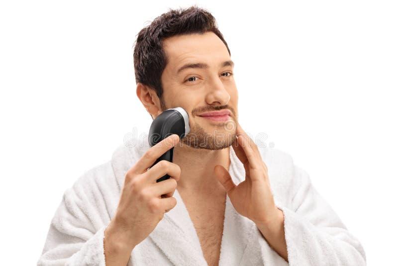 Stilig grabb som klipper hans skägg med en rakapparat arkivfoton
