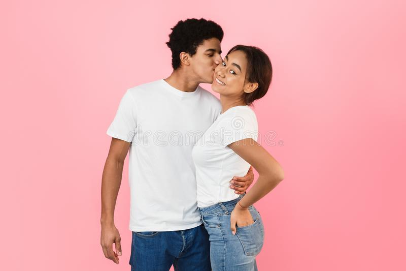 Stilig grabb som kramar flickvännen och kysser henne i kind royaltyfria bilder