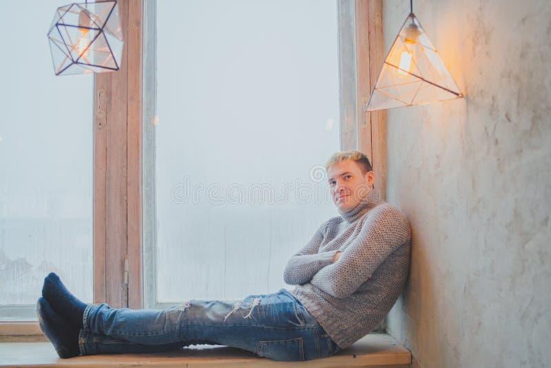 Stilig grabb som sitter p? f?nsterbr?dan p? bakgrunden av ett stort f?nster arkivfoto