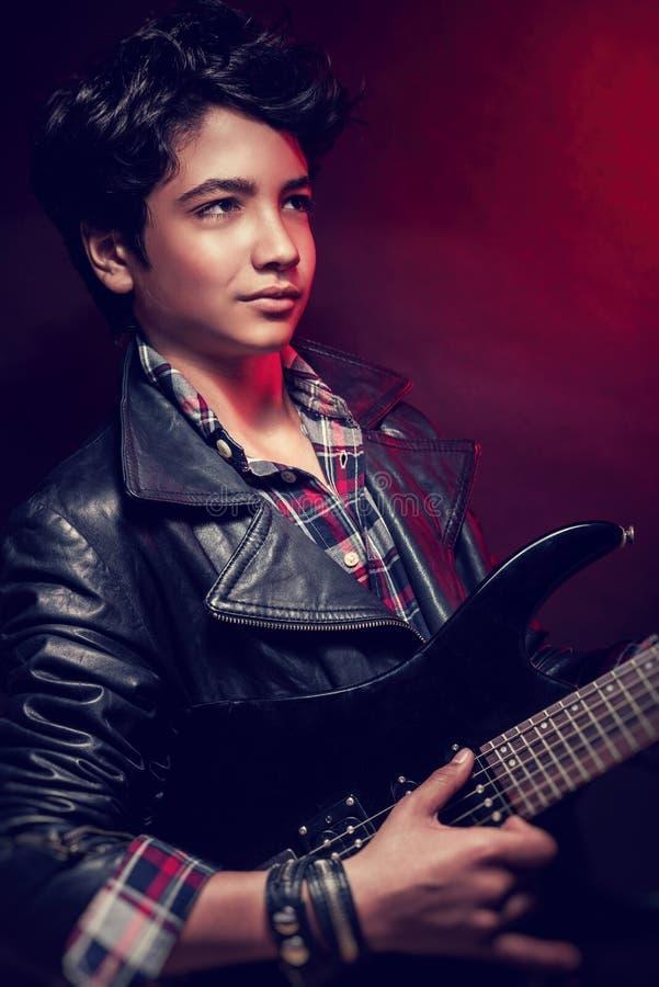Stilig grabb som spelar på gitarren royaltyfria foton