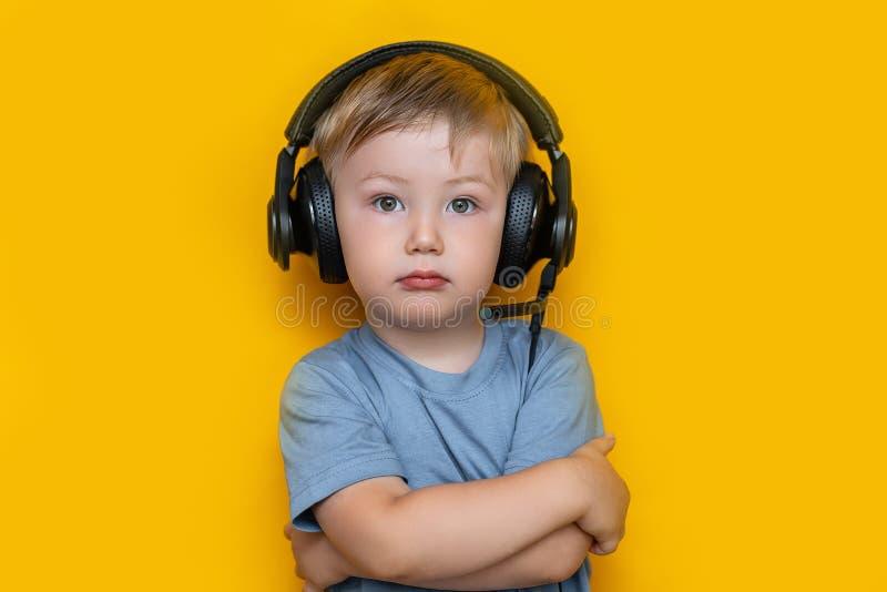 Stilig gullig blond pys tre gamla år, i att spela svart hörlurar blick på kameran, gråa ögon och den gråa t-skjortan på guling fotografering för bildbyråer