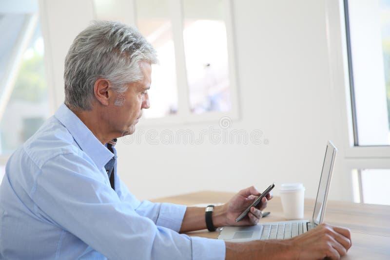 Stilig hög affärsman som arbetar på bärbara datorn arkivbild