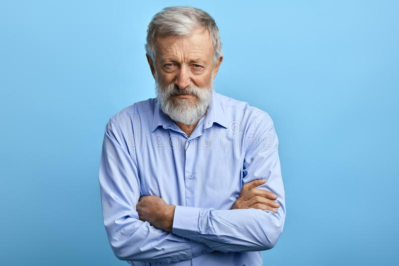 Stilig hög man i blå skjorta med skeptikeruttryck fotografering för bildbyråer