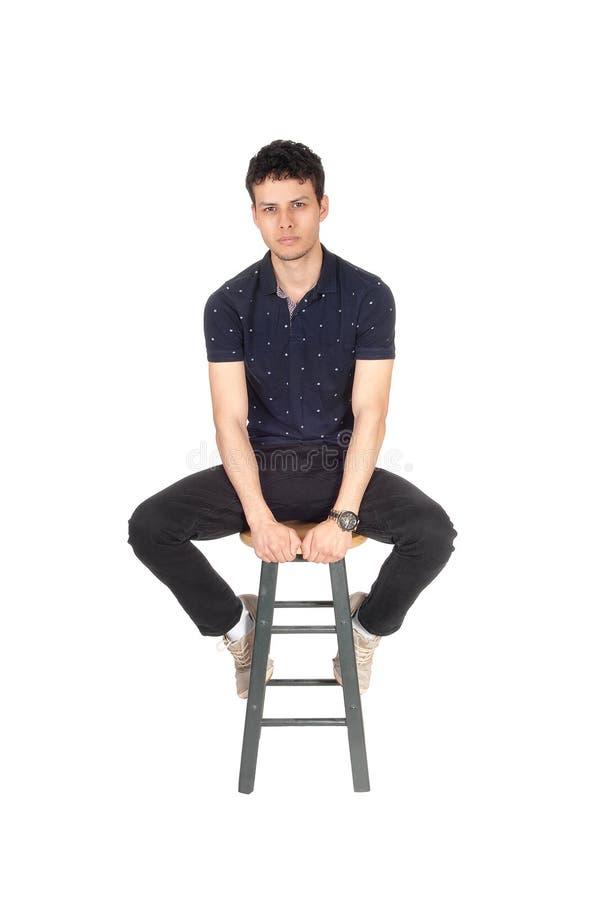 Stilig högväxt ung man som sitter på stol i studion arkivbild