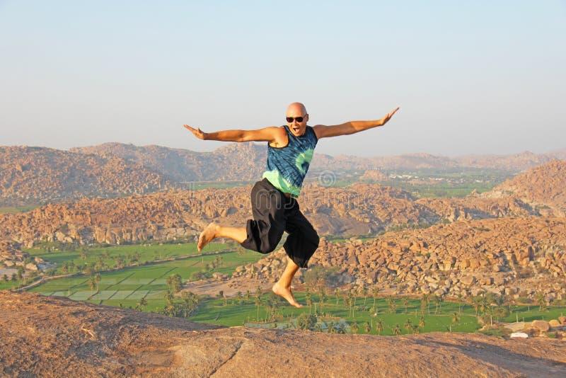 Stilig höjdhoppman Bärande solglasögon för en skallig man i Hampi, hopp högt på den Anjaneya kullen, Hanuman Temple Risfält eller royaltyfri foto