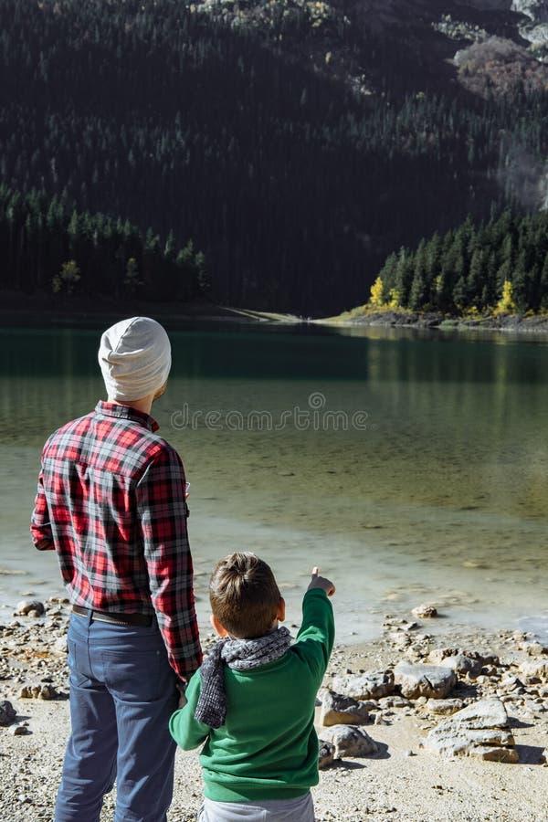 Stilig handelsresande med sonen som ser på den svarta sjön, Montene arkivbild