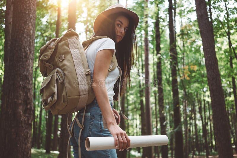 Stilig handelsresandekvinna med ryggsäck- och hattanseende i den unga hipsterflickan för skog som går bland träd på solnedgång royaltyfri fotografi