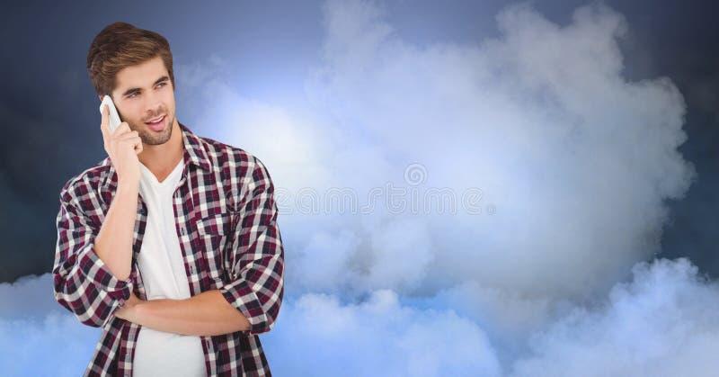 Stilig hipster som använder mobiltelefonen mot molnig himmel arkivfoto