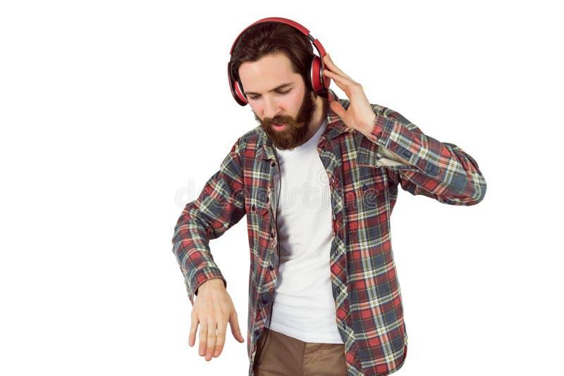 Stilig hipster som tycker om att lyssna till musik royaltyfri foto