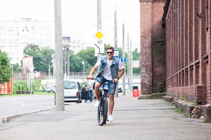 Stilig hipster som tycker om stadsritt med cykeln royaltyfri fotografi