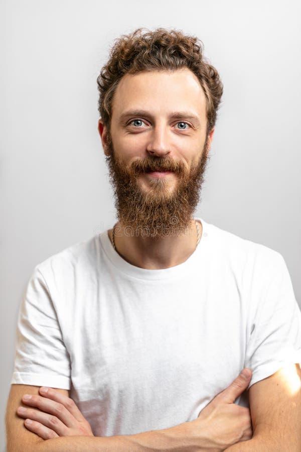 Stilig hipsterman med skägget som ler på kameran över vit bakgrund arkivbilder