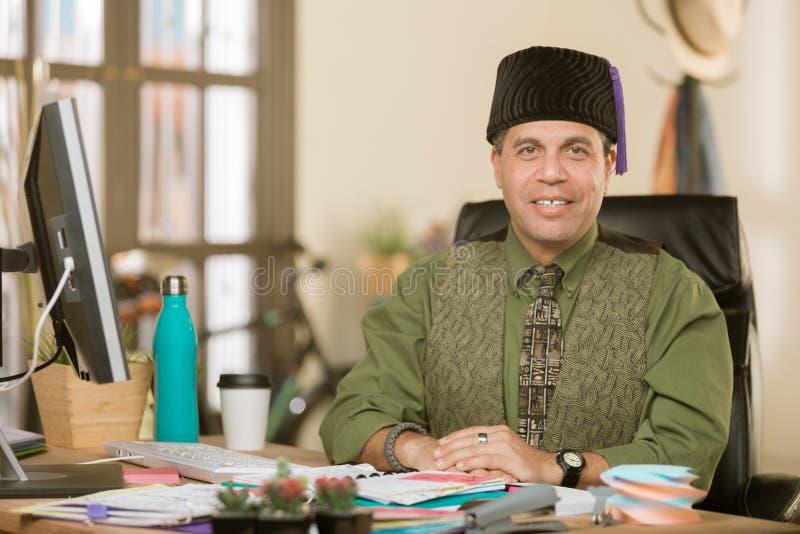 Stilig idérik affärsman i ett kontor som bär en Fez arkivfoto