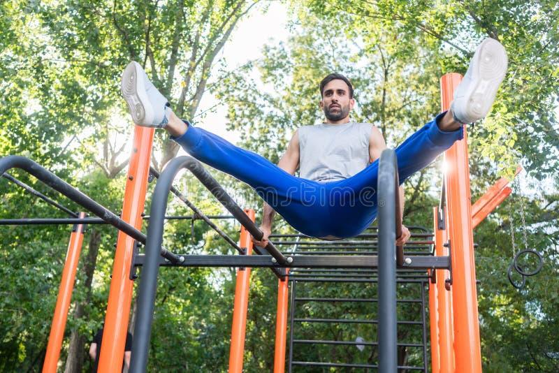 Stilig idrotts- ung man som övar vertikal benlönelyft i arkivbild