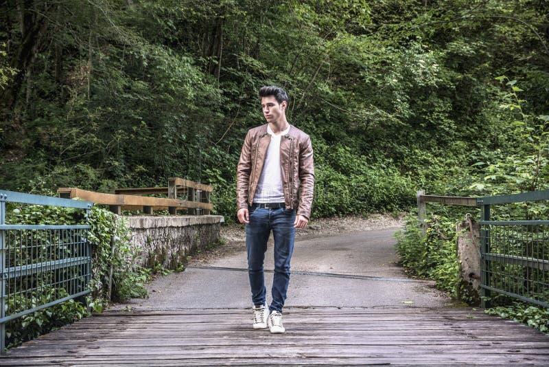 Stilig idrotts- ung man som in fotvandrar på bron royaltyfri bild