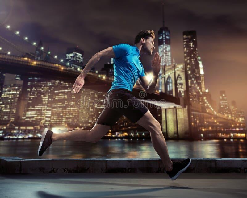 Stilig joggerspring till och med staden i natten royaltyfri bild