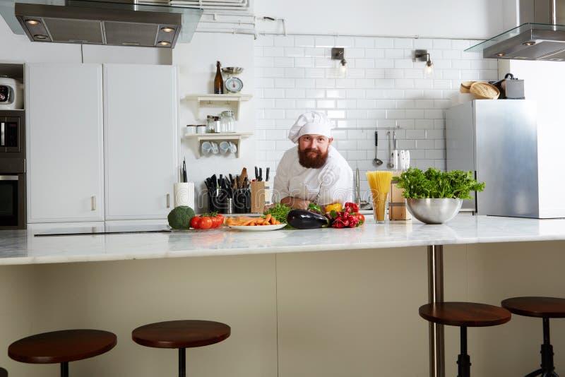 Stilig kock i enhetligt anseende på stort kök royaltyfri bild