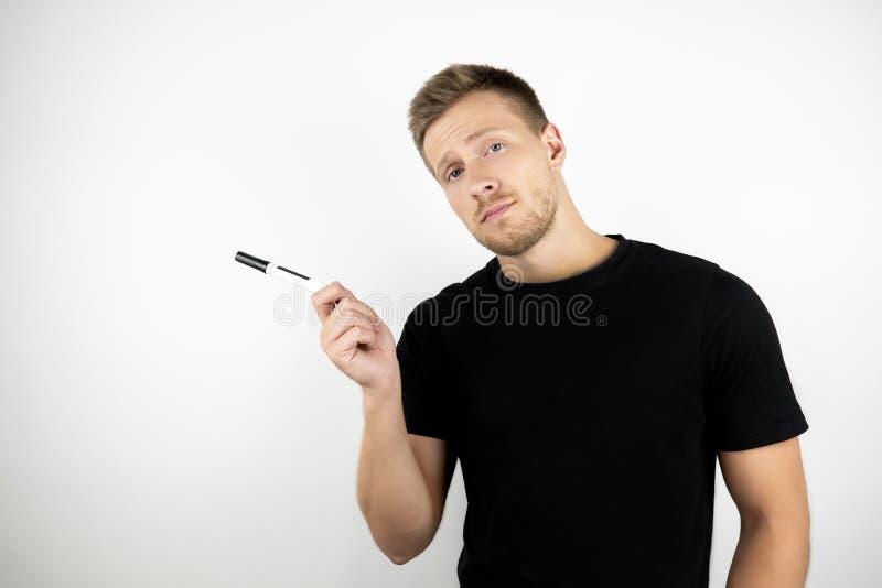Stilig kontorsarbetare för ung man som bär den svarta t-skjorta innehavmarkören för anmärkningar som skriver isolerad vit bakgrun royaltyfri bild