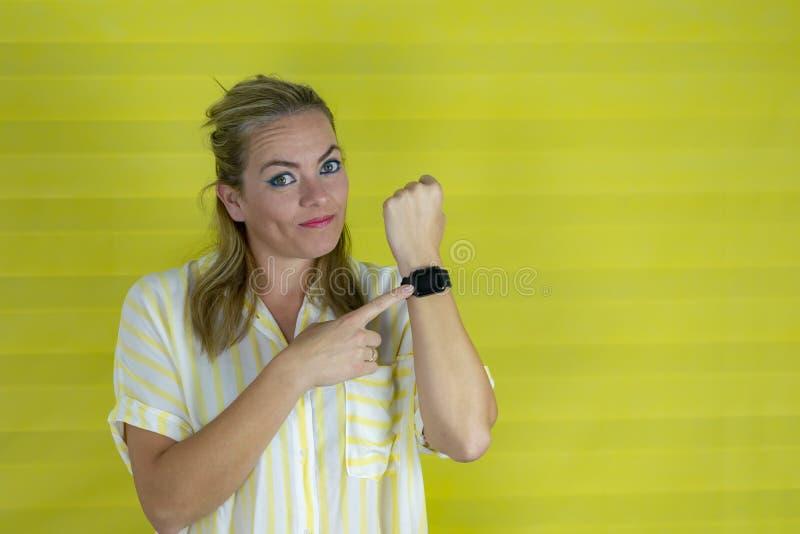 Stilig kvinna i brådska som pekar för att hålla ögonen på tid, otålighet, rubbning och ilsket för stopptidfördröjning arkivbild