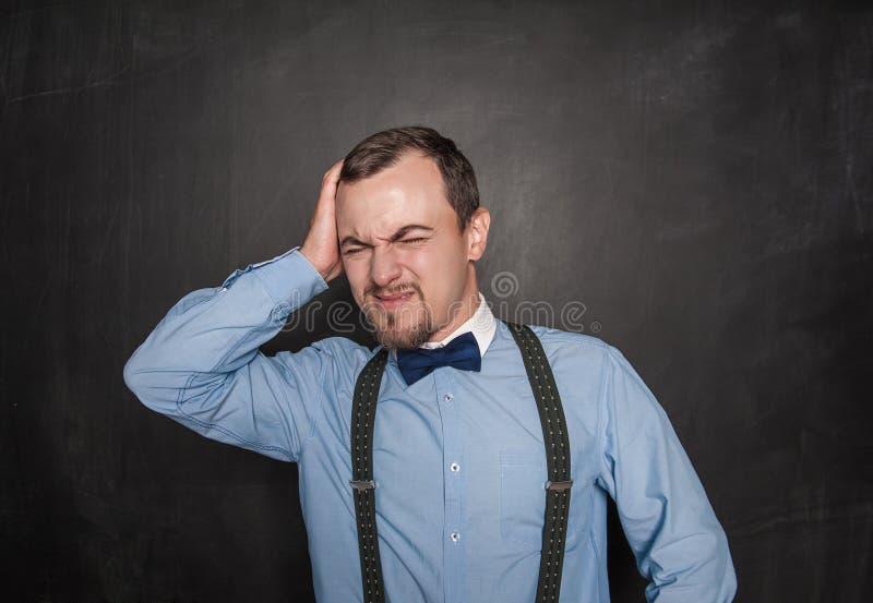 Stilig lärareman med huvudvärk på svart tavla royaltyfri bild