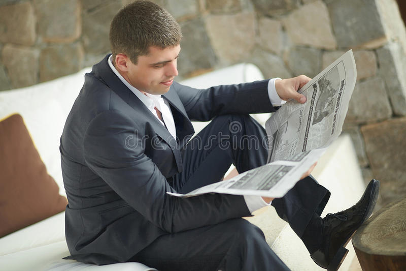 Stilig läs- morgontidning för ung man i svart dräkt arkivfoton