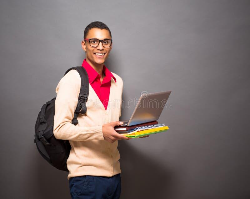 Stilig latinsk student med bärbar datordatoren i studio royaltyfri fotografi