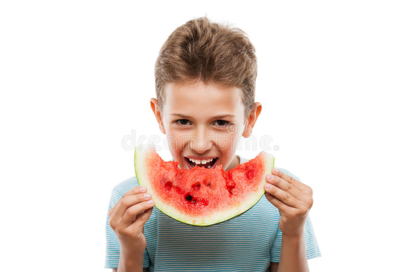 Stilig le barnpojke som rymmer den röda vattenmelonfruktskivan arkivbild