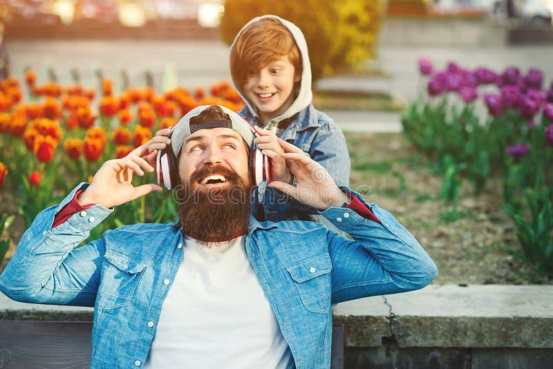 Stilig le fader och hans son som tycker om musik på staden Fader och unge som tillsammans spenderar tid utomhus Den lyckliga fami royaltyfri bild