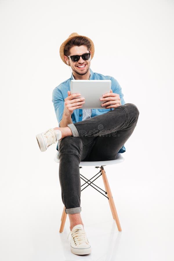 Stilig le man som använder minnestavlan och sitter på stolen royaltyfri bild