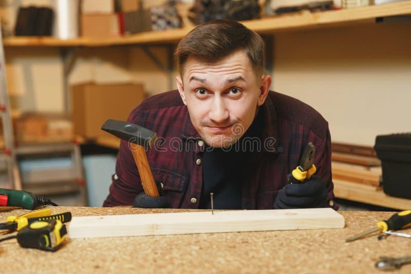 Stilig le ung man som arbetar i snickeriseminarium på trätabellstället med stycket av trä fotografering för bildbyråer