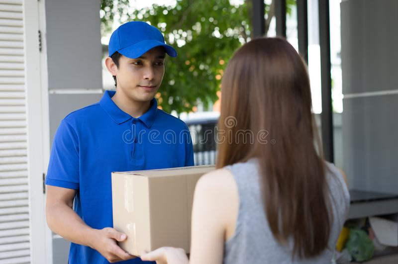 Stilig leveransperson för ung man i blått enhetligt hållande kort arkivbild