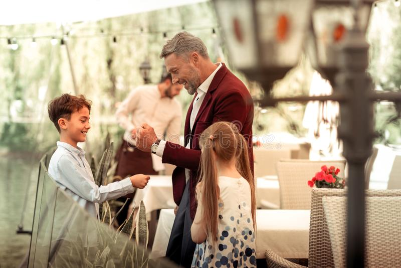 Stilig liten son som känner lyckligt möte hans fader för lunch arkivbilder